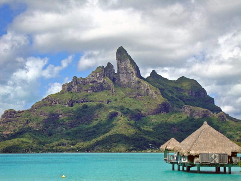 View of Mount Otemanu towering over the Bora Bora lagoon and resort bungalows.